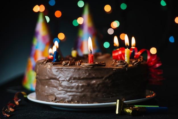 光の背景とパーティー帽子に対して照らされたキャンドルで誕生日ケーキ