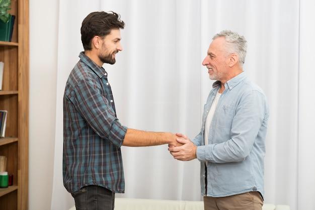 若い幸せな男の手を繋いでいる高齢者の男
