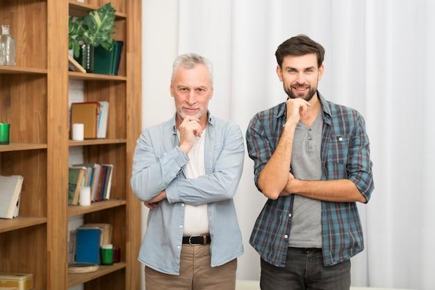 高齢男性と部屋のあごの近くに手を持つ若い男