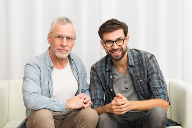Пожилой улыбающийся мужчина и молодой счастливый парень, сложив руки на диване