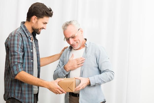 Молодой парень дарит подарок пожилому счастливому мужчине