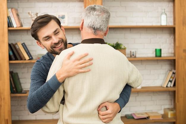 本棚の近くの老人とハグする若い幸せな男
