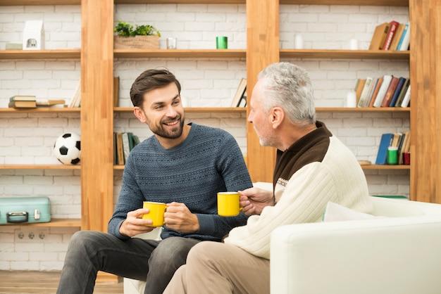 笑みを浮かべて男とソファの上のカップを持つ老人