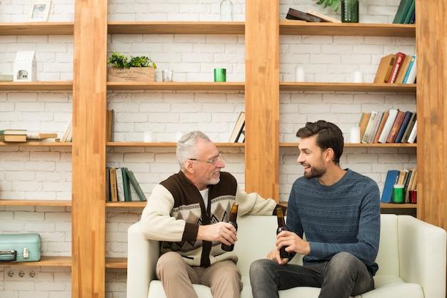 若い微笑の男とソファの上の瓶を持つ老人