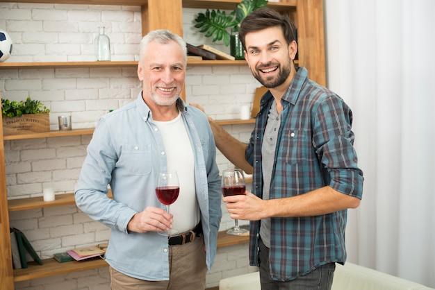 高齢者の男性とワインのグラスを持つ若い微笑の男