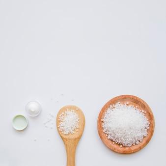 白い背景の上の純粋な岩塩と保湿クリーム