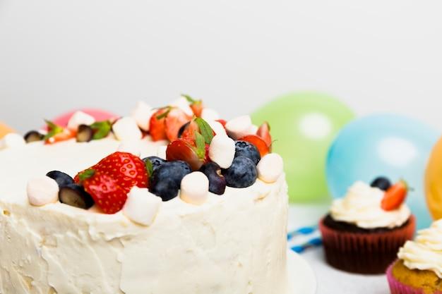 テーブルの上のカップケーキの近くのさまざまな果実と大きなケーキ