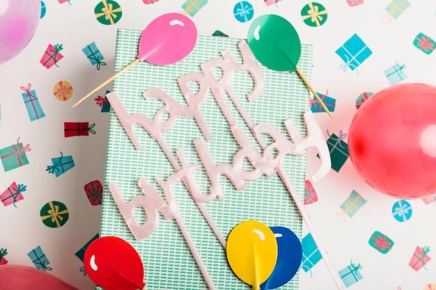 Подарочная коробка и знак с днем рождения между орнаментом и яркими воздушными шарами