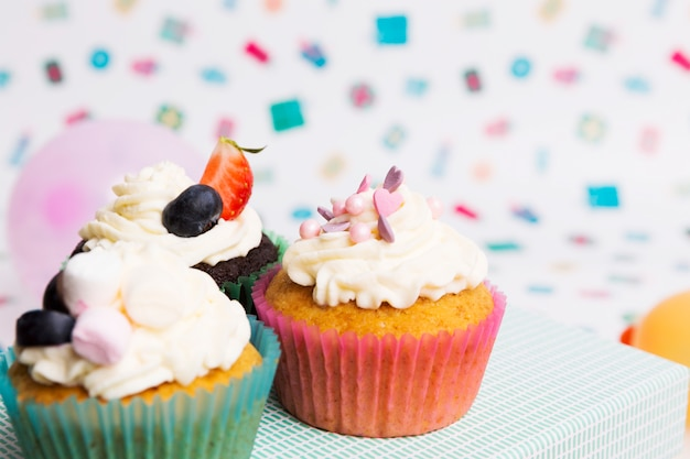 Вкусные кексы возле ярких воздушных шаров
