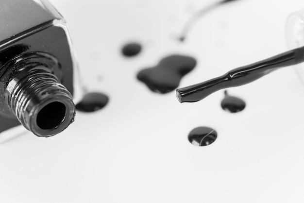 Черная пролитая бутылка лака для ногтей на белом фоне