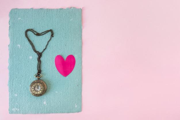 古い懐中時計と青い紙の上の小さな心