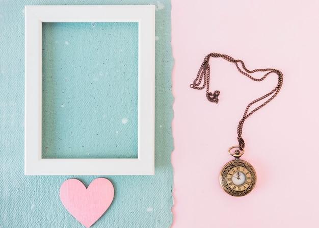 古い懐中時計の近くの青い紙の上のフォトフレームと飾りの心