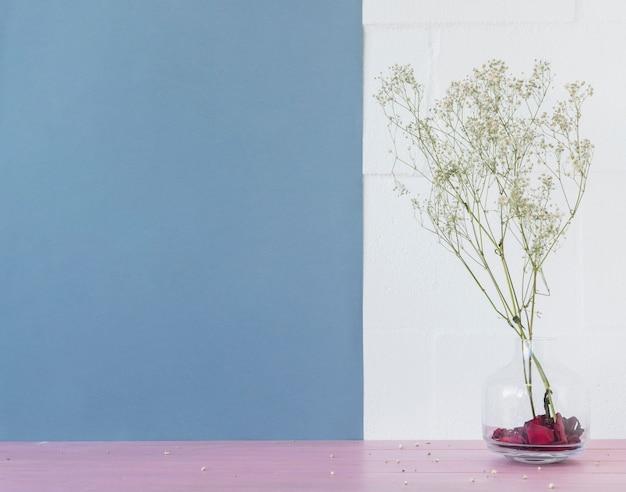 レンガの壁の近くの花瓶に緑の植物の小枝