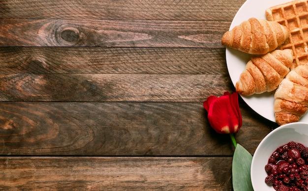 Пекарня на тарелке возле варенья и цветов