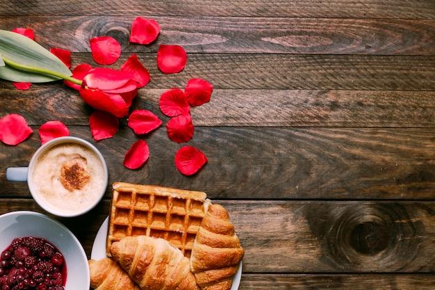 Варенье в миске, свежий цветок, пекарня, лепестки и чашка напитка