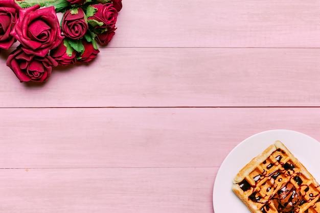 テーブルの上の赤いバラの花束とベルギーワッフル