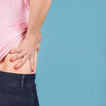 青色の背景に彼女のより低い背中の痛みを持つ女性