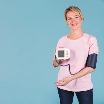 Улыбается женщина, показывая результаты кровяного давления на экране электрического тонометра