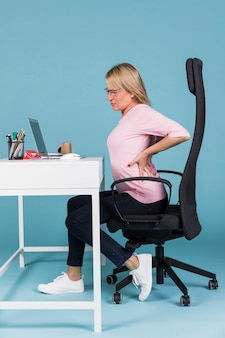 ラップトップに取り組んでいる間腰痛に苦しんでいる椅子に座っている女性