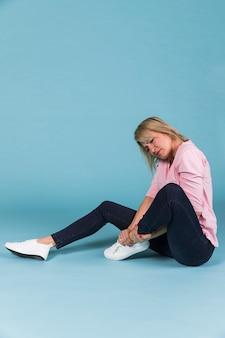 青色の背景に座っているけがをした足を持つ女性