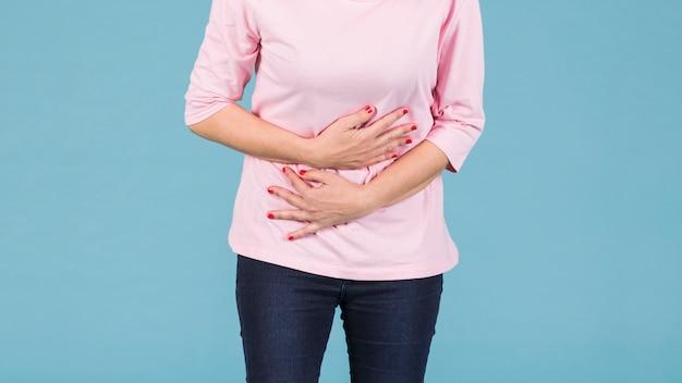 青い背景に対して立っている胃の痛みを持つ女性の中央部
