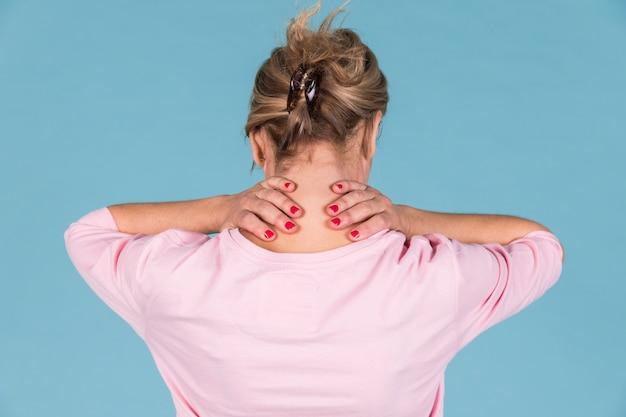 青い壁紙に対して首の痛みに苦しんでいる女性の背面図