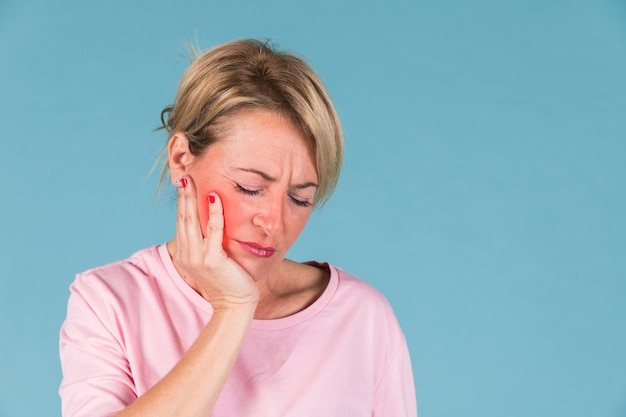 青色の背景の前に歯痛を持つ病気の女性のクローズアップ
