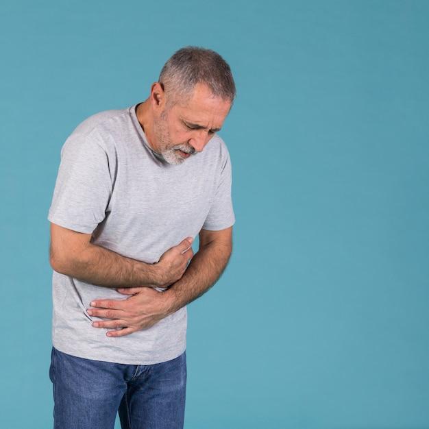 青い背景の前に胃の痛みを持つ年配の男性