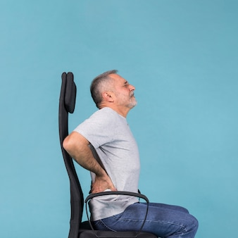 青色の背景に背中の痛みを持っている椅子に座っている年配の男性人