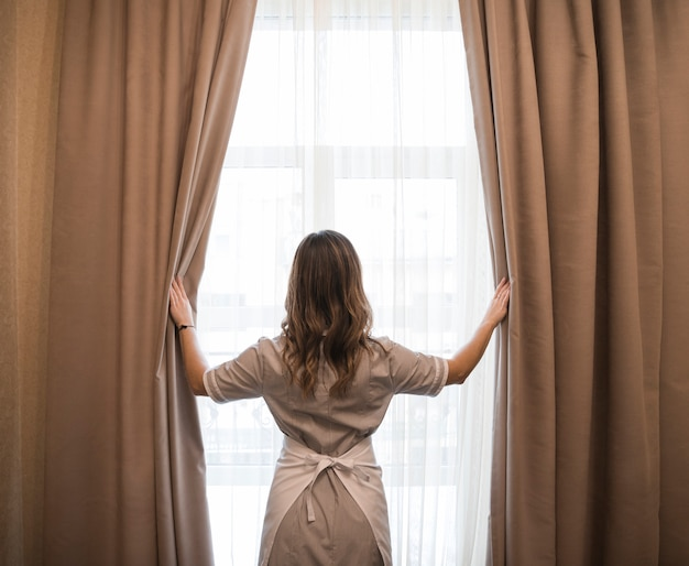 ホテルの部屋でカーテンを開く若いメイドの後姿