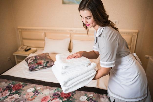 ベッドシートに新鮮な白いバスタオルのスタックを置くメイドのクローズアップ