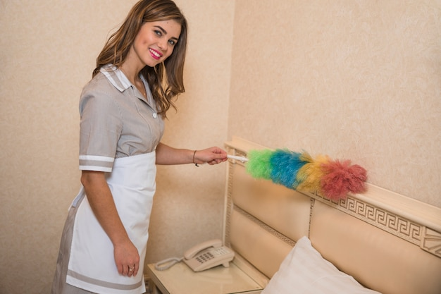 柔らかい羽根でほこりを掃除するメイドの肖像画を笑顔