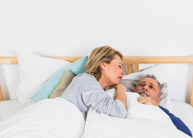 ベッドの上の羽毛布団で悲しい男の近くに横たわっている高齢者の女性