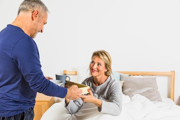 ベッドの上の羽毛布団で笑顔の女性に朝食を与える老人