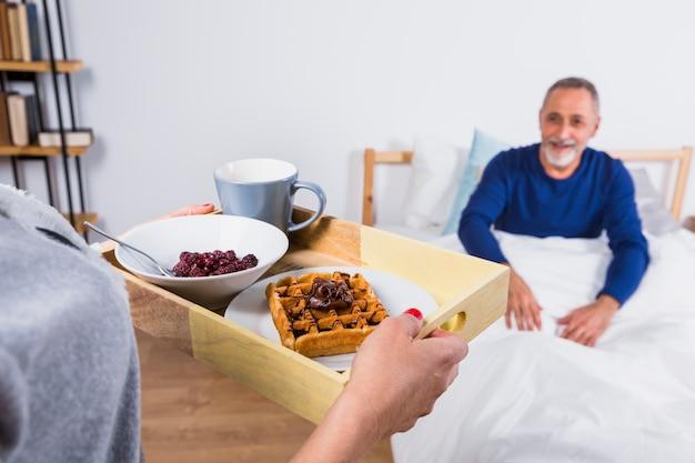 ベッドの上の羽毛布団で高齢者の笑みを浮かべて男の近くの朝食を持つ女性