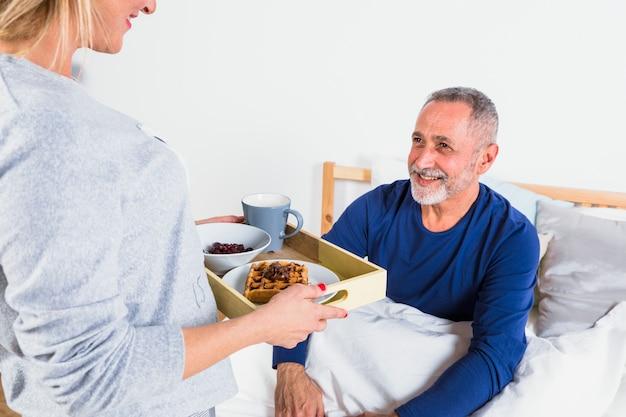 ベッドの上の羽毛布団で笑みを浮かべて男に朝食を与える高齢者の女性