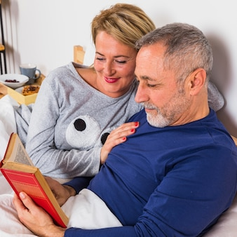 ベッドの上の羽毛布団で本を持つ男の近くの高齢者の笑顔の女性