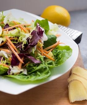 テーブルの上のレモンと皿の上の野菜サラダ