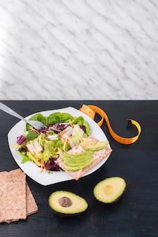 Овощной салат с зеленым авокадо на хрустящем хлебе