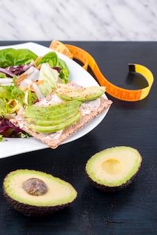 Овощной салат с авокадо на хрустящем хлебе на столе