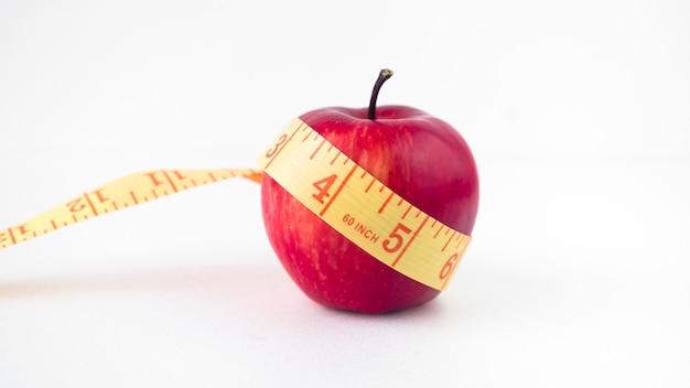 測定テープとテーブルの上のリンゴ