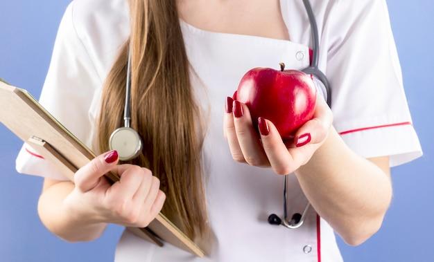 医者の赤いリンゴを手で押し