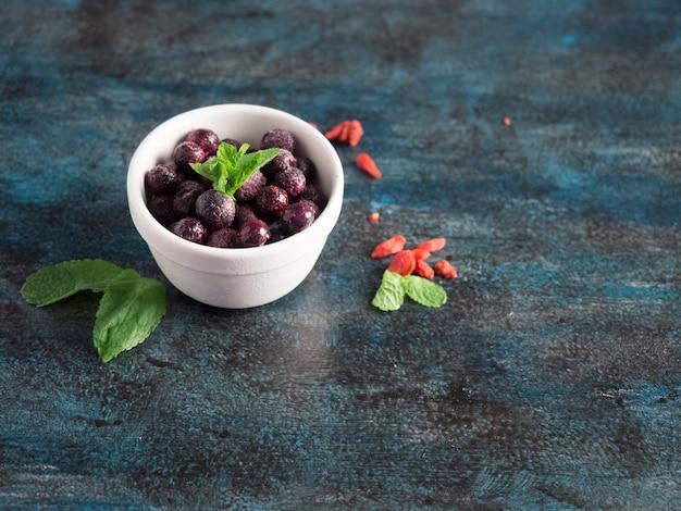 青いテーブルの上のボウルに冷凍果実