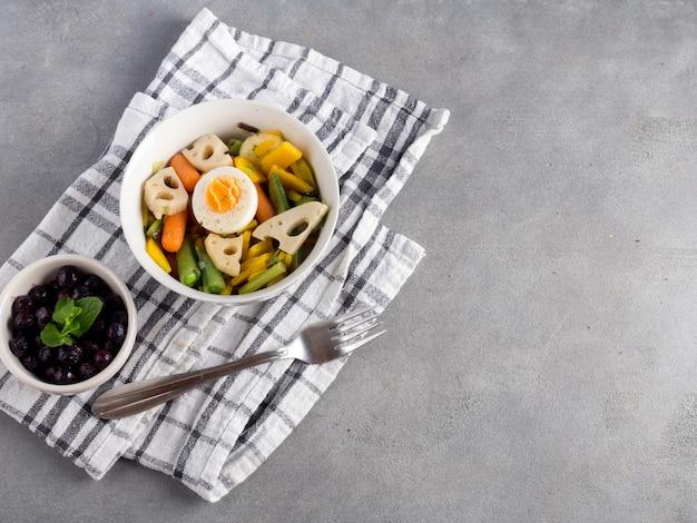 灰色のテーブルの上の果実とベジタリアンサラダ