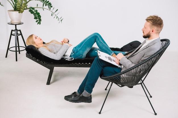 ソファの上に横たわる落ち込んで若い女性患者と心理学者の診断インクブロットテストロールシャッハ