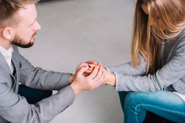 彼女のメスの患者に耳を傾けながら一緒に彼の手を保つ心理学者のクローズアップ