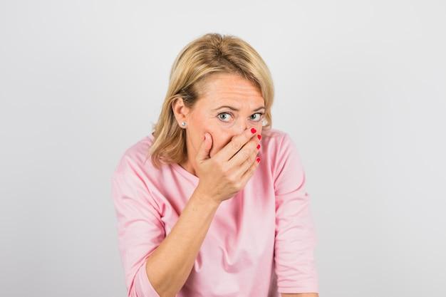手で顔を閉じるピンクのブラウスで年配の女性