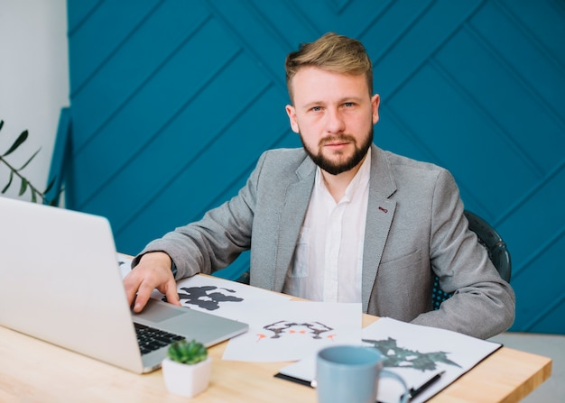 ラップトップを使用してロールシャッハ・インクブロットテスト紙で彼のオフィスに座っている男性の心理学者の肖像画