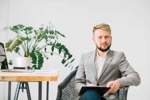クリップボードにメモを書く彼のオフィスに座っている男性の心理学者の肖像画