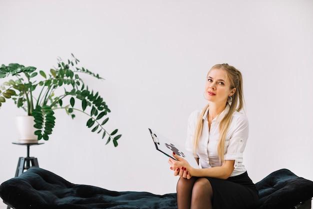 クリップボードにロールシャッハ・インクブロットテスト紙を保持しているソファに座っている女性の心理学者